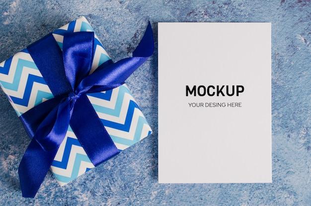 Tarjeta de felicitación y caja de regalo con papel blanco en blanco