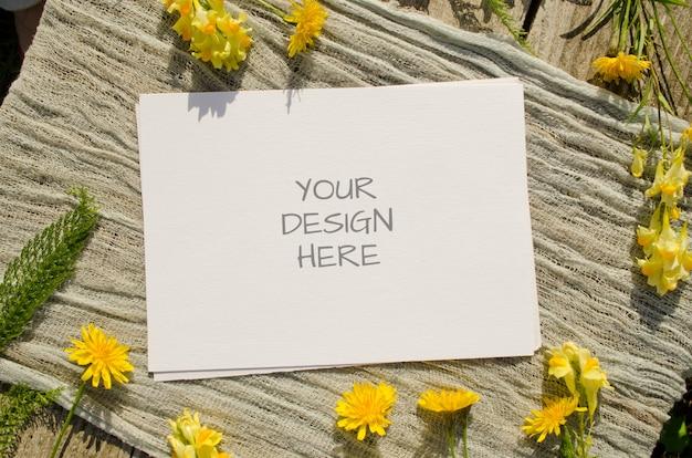 Tarjeta de felicitación de maqueta de papelería de verano o invitación de boda con flores amarillas en una madera vieja