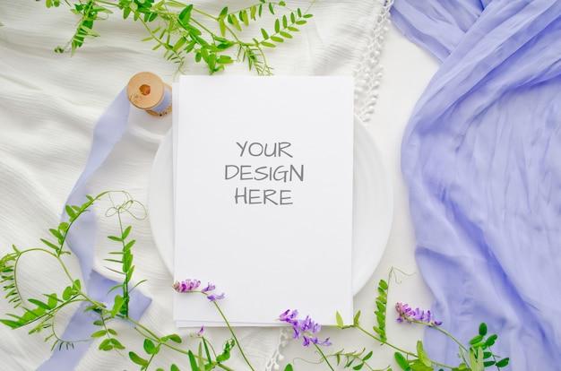 Tarjeta de felicitación de maqueta de papelería de verano o invitación de boda con flores violetas y delicadas cintas de seda en un espacio en blanco