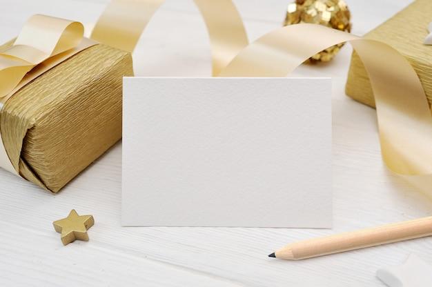 Tarjeta de felicitación de navidad de maqueta con cinta de regalo dorada