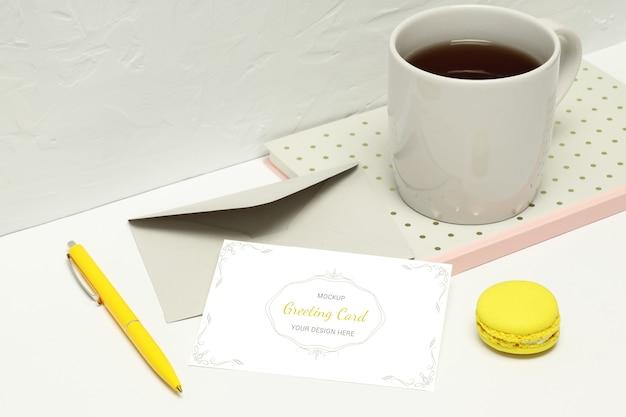 Tarjeta de felicitación con notas, sobre, pluma, macaron y taza de té
