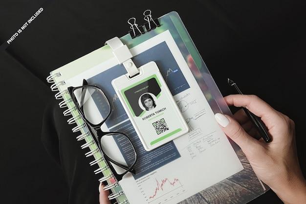 Tarjeta de identificación de plástico en el bloc de notas en espiral en maqueta de manos de mujer