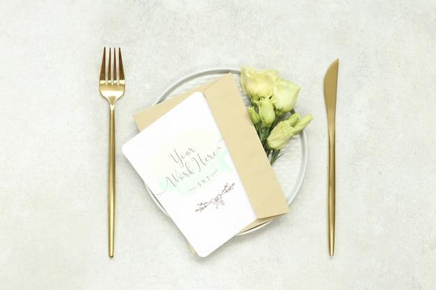 Tarjeta de invitación de boda de maqueta en plato y cubiertos de oro