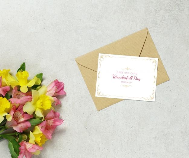 Tarjeta de invitación falsa sobre fondo gris con flores y sobre