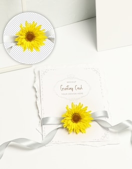 Tarjeta de invitación, flor amarilla y cinta gris sobre fondo blanco