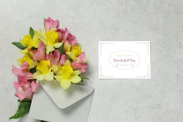 Tarjeta de invitación con flores amarillas y rosadas, sobre gris.