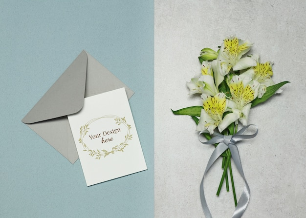 Tarjeta de invitación con flores sobre fondo azul gris