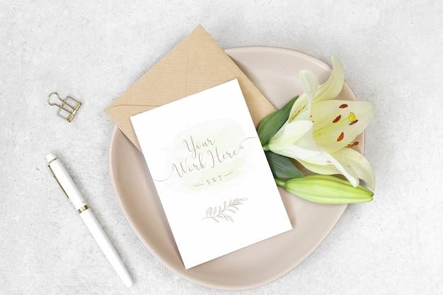 Tarjeta de invitación de maqueta con bolígrafo blanco y flores.