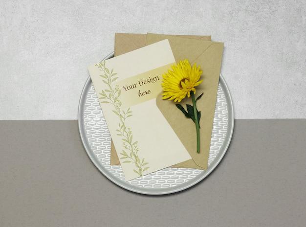 Tarjeta de invitación de maqueta con flor amarilla sobre fondo beige gris