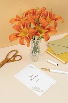 Tarjeta de invitación de maqueta con flores naranjas, notas y tijeras doradas.