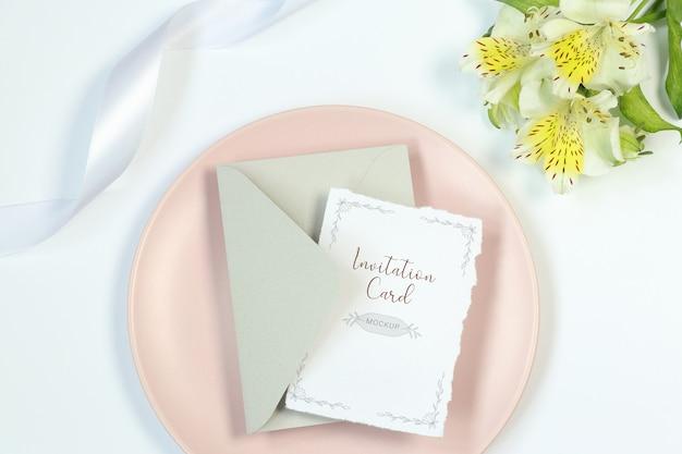 Tarjeta de invitación de la maqueta sobre fondo blanco con flores, sobre gris y cinta