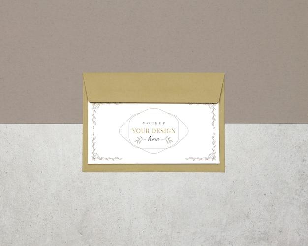 Tarjeta de invitación de la maqueta, sobre en fondo gris beige