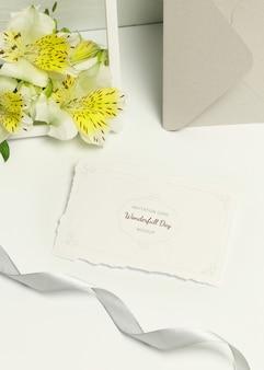 Tarjeta de invitación sobre fondo blanco, ramo de flores y sobre gris.