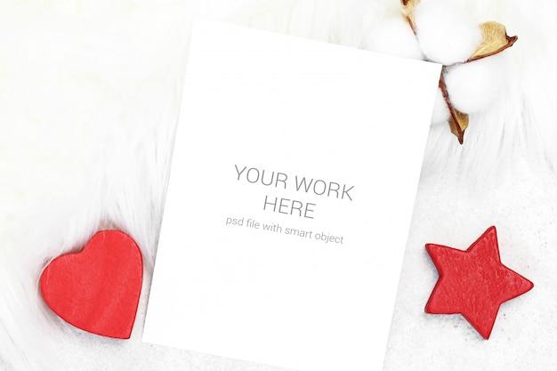 Tarjeta de maqueta con algodón y juguetes rojos.