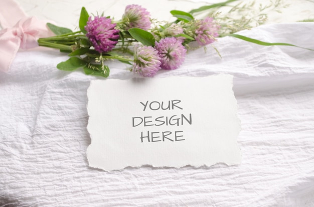 Tarjeta de maqueta de boda con bordes irregulares con flores rosas y delicadas cintas de seda sobre un fondo blanco.