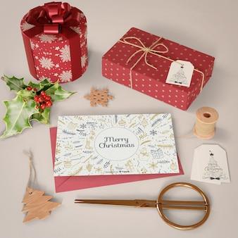 Tarjeta de navidad y colección de regalos en la mesa