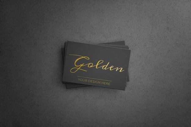 Tarjeta de negocios negra con diseño dorado.