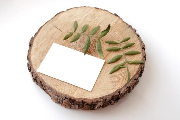 Tarjeta de papelería maqueta en un asador de madera con hojas de pistachos