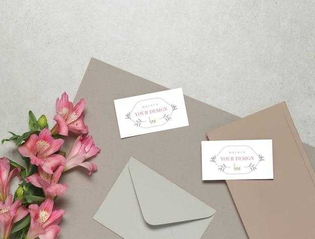 Tarjeta de visita de la maqueta en fondo gris, flores frescas, sobre gris y notas rosadas