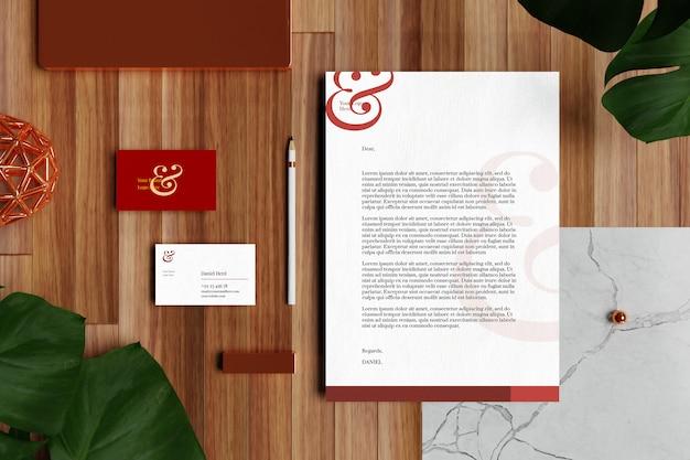 Tarjeta de visita con membrete documento a4 y maqueta de papelería en piso de madera