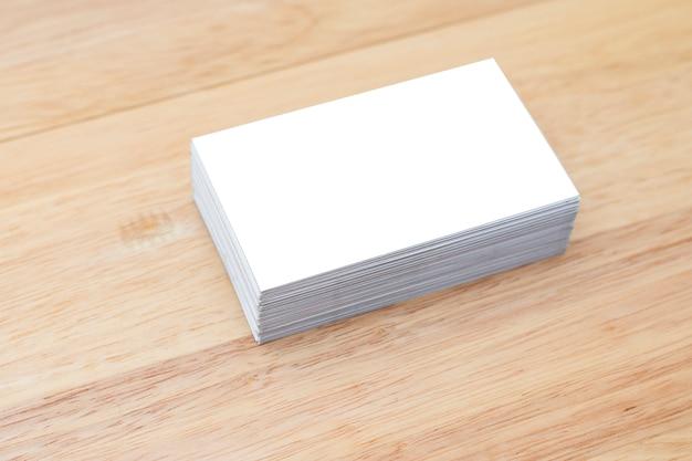 Tarjetas de visita en blanco apilan maqueta en mesa de madera