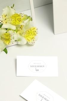 Tarjetas de visita de la maqueta en el fondo blanco, las flores frescas y el marco