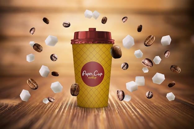 Taza de café de papel y frijoles en maqueta de gravedad psd gratis