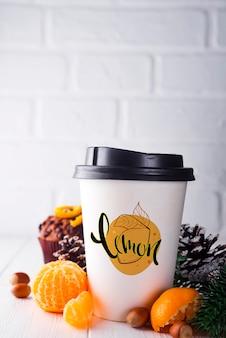Taza de café de papel rodeada de adornos navideños