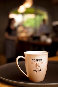 Taza de café en un plato con fondo borroso