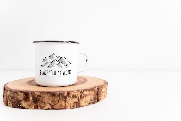 Taza de esmalte blanco en maqueta de tablero de corte de madera rústica. estilo boho