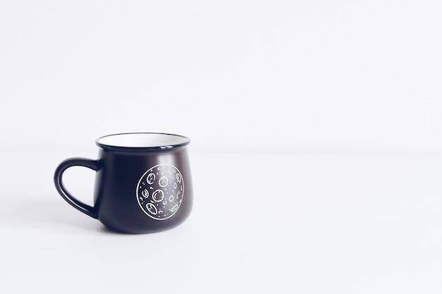 Taza de esmalte negro sobre maqueta de mesa blanca.