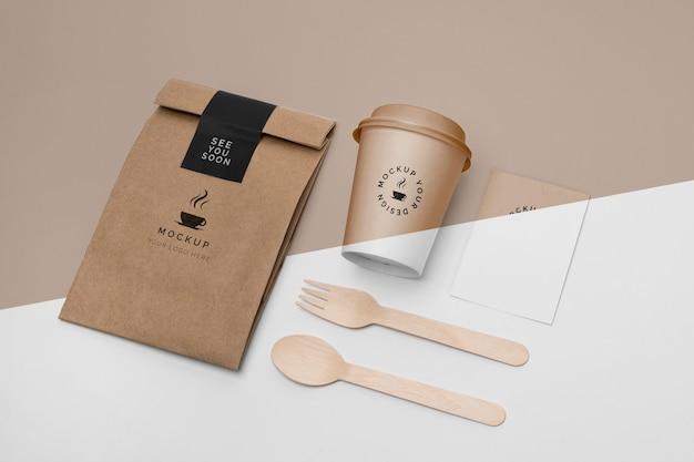 Taza de plástico y bolsa de papel con maqueta de café.