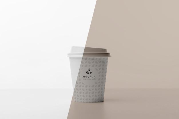 Taza de plástico con café simulado en la mesa