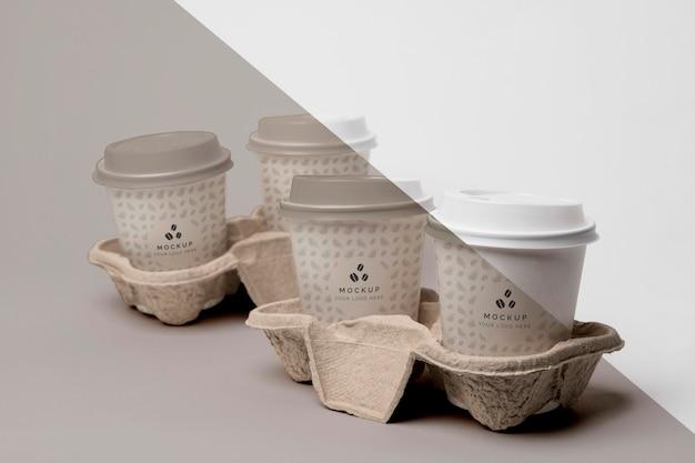 Taza de plástico con maqueta de café en apoyo.