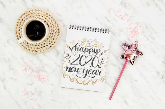 Tazza di caffè e blocco note di vista superiore con la citazione del nuovo anno