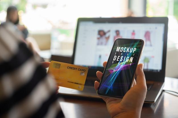 Telefono cellulare del modello con la carta di credito per acquisto online nel concetto di internet