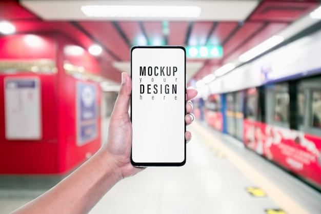 Telefono cellulare del modello con la vista vaga della metropolitana rossa