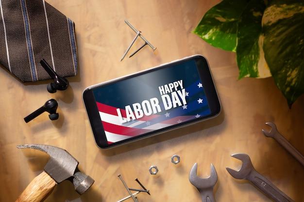 Telefono cellulare del modello per il concetto di festa del lavoro.