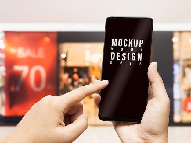 Telefono cellulare mockup con negozio di abbigliamento sfocato e segno di sconto.