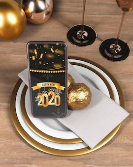 Telefono con messaggio per il nuovo anno sulla piastra