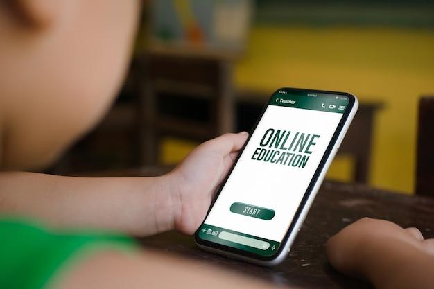 Telefono della tenuta del bambino dello smartphone del modello in aula per il concetto online di istruzione