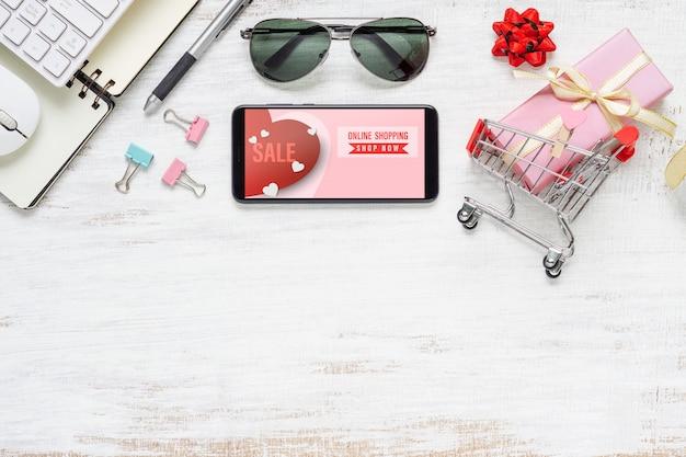 Teléfono inteligente, gafas de sol y carrito de compras para compras en línea por internet