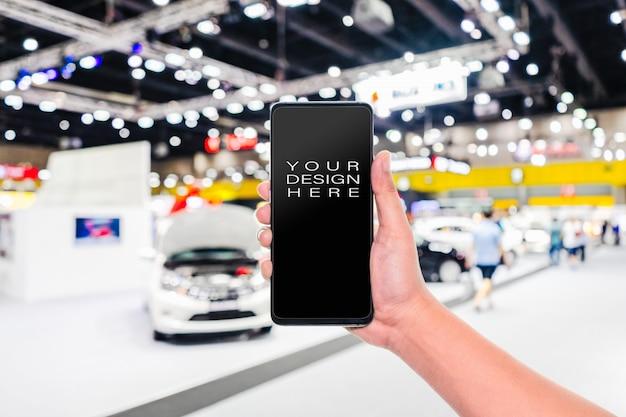 Teléfono móvil con espectáculo de exposición de coches borrosa abstracta