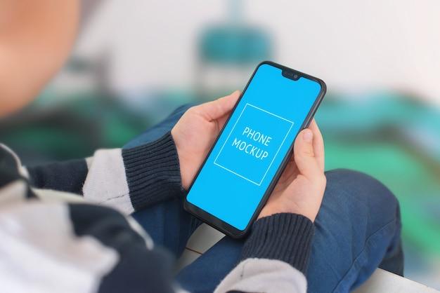 Telefoon mockup in handen van het kind. moderne smartphone met dunne randen.