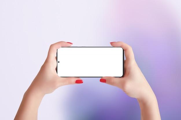 Telefoon mockup in horizontale positie in handen van de vrouw. paarse abstracte achtergrond