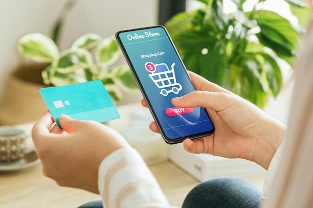 Telefoonmodel dat wordt vastgehouden door een vrouw die thuis een bestelling online betaalt