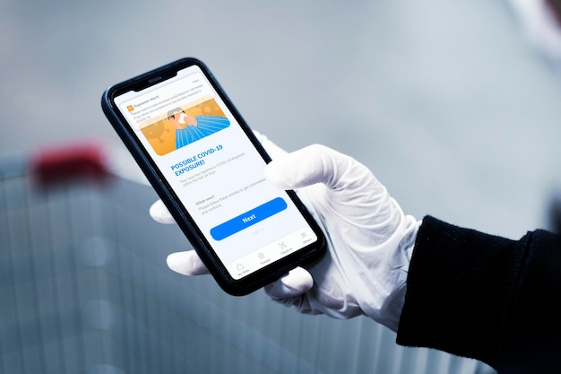 Telefoonmodel met persoon die handschoenen draagt en het apparaat vasthoudt