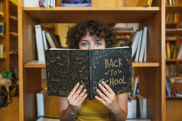 Terug naar schoolconcept met het boek van de meisjeslezing in bibliotheek