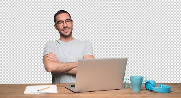 Tevreden jonge man zit aan zijn bureau