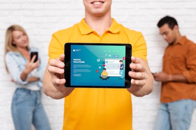 Texto de soluciones digitales en tableta con personas desenfocadas en segundo plano